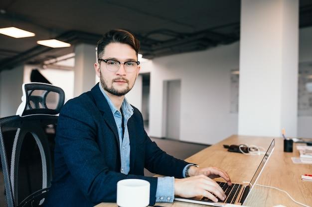 Jonge donkerharige man werkt aan de tafel in kantoor. hij draagt een blauw shirt met een zwarte jas. hij typt op laptop en kijkt naar de camera.
