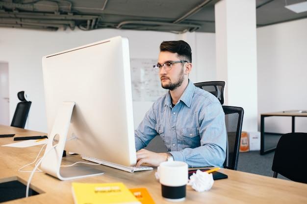 Jonge donkerharige man werkt met de computer op zijn bureaublad in kantoor. hij draagt een blauw shirt en ziet er druk uit.