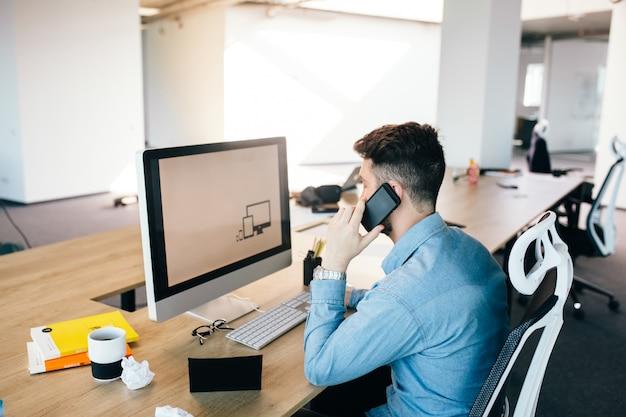 Jonge donkerharige man werkt met een computer en praat aan de telefoon op zijn bureaublad in kantoor. hij draagt een blauw shirt en ziet er druk uit.