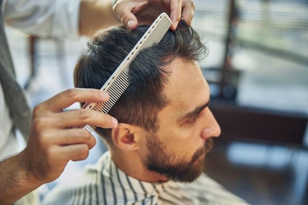 Jonge donkerharige mannelijke kapperszaak die naar zichzelf in de spiegel kijkt terwijl zijn haar wordt gekamd