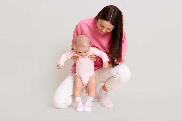 Jonge donkerharige mooie moeder draagt casual trui en broek met baby baby, mama leert dochter lopen en kijken naar kind, poseren geïsoleerd op een witte muur.