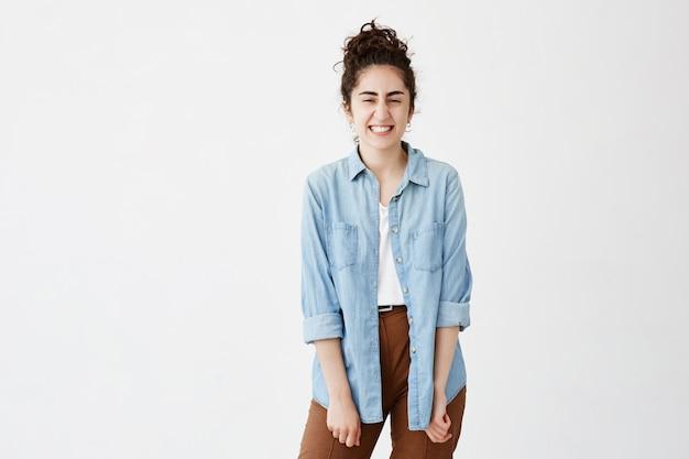 Jonge donkerharige vrouw balt tanden van vreugde, gekleed in denim shirt over witte top, met een goed humeur. gezichtsuitdrukking, gevoelens en emoties