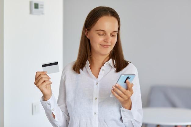 Jonge donkerharige vrouw die een wit overhemd draagt met een creditcard en gegevens invoert in een smartphone voor online betalingen, kijkend naar het apparaatscherm met positieve uitdrukking.
