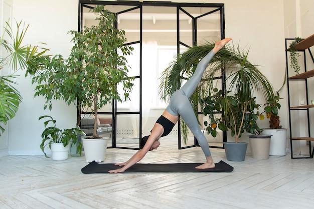 Jonge donkerharige vrouw die 's ochtends yoga beoefent bij haar thuis in de buurt van planten. de vrouw houdt zich bezig met zelfbeschikking en doet yoga-oefeningen.