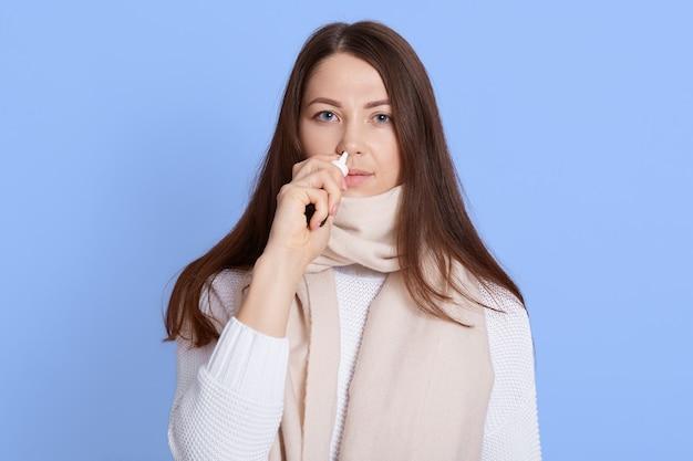 Jonge donkerharige vrouw, gekleed in witte trui en sjaal staande druipende neusdruppels geïsoleerd op blauwe muur, zieke dame kijkt camera met verstoorde gezichtsuitdrukking.