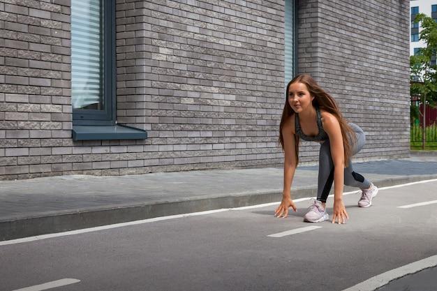 Jonge donkerharige vrouw sportvrouw in een sportieve korte top en gym legging glimlacht en strekt haar benen op een zomerdag in een moderne stedelijke binnenplaats