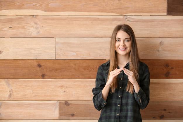 Jonge doofstomme vrouw die gebarentaal op houten achtergrond gebruikt