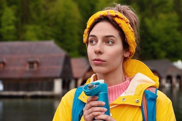 Jonge doordachte blanke vrouw draagt gele sjaal en anorak