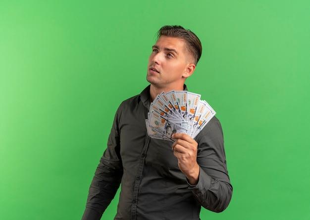 Jonge doordachte blonde knappe man houdt geld en kijkt omhoog geïsoleerd op groene achtergrond met kopie ruimte