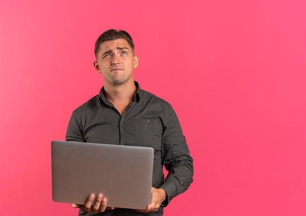 Jonge doordachte blonde knappe man houdt laptop en kijkt omhoog geïsoleerd op roze achtergrond met kopie ruimte