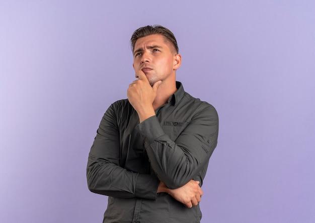 Jonge doordachte blonde knappe man legt de hand op de kin en kijkt omhoog geïsoleerd op violette achtergrond met kopie ruimte