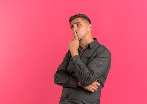 Jonge doordachte blonde knappe man legt hand op kin opgezocht geïsoleerd op roze achtergrond met kopie ruimte