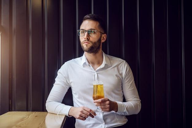 Jonge doordachte geeky zakenman leunend op de tafel naast het raam en kijkt er doorheen, houdt een glas bier vast en ontspant na het werk.