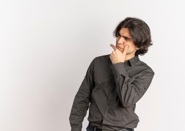 Jonge doordachte knappe blanke man legt de hand op de kin en kijkt naar kant geïsoleerd op een witte achtergrond met kopie ruimte
