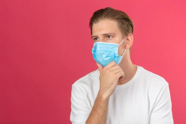 Jonge doordachte man in medische beschermend masker kin aan te raken en na te denken over geïsoleerde roze achtergrond