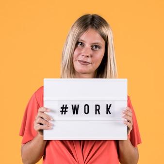 Jonge dove vrouw die lichtvak met het werktekst van de hashmarkering op gele achtergrond toont