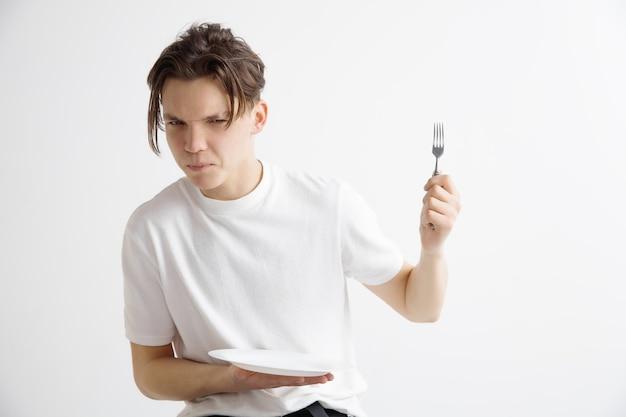 Jonge droevige aantrekkelijke kerel die lege schotel en vork houdt die op grijze muur wordt geïsoleerd.