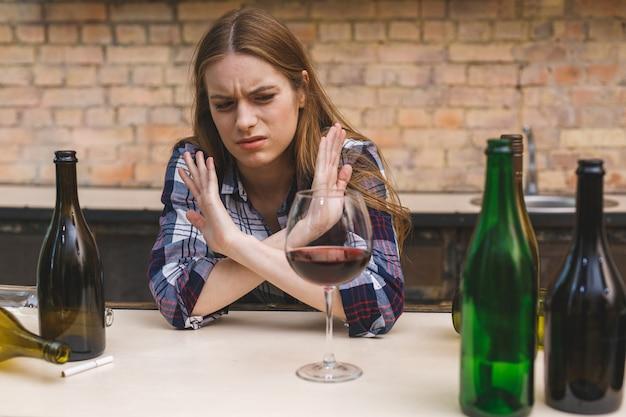 Jonge droevige en verspilde alcoholische vrouw die aan keukenbank zit die rode wijn drinkt, volledig dronken die depressief eenzaam kijkt en kater lijdt in alcoholisme en alcoholmisbruik.