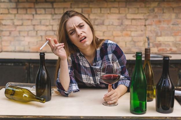 Jonge droevige en verspilde alcoholische vrouw die bij keukenbank zit die rode wijn drinkt die glas volledig dronken houdt die depressief eenzaam kijkt en kater lijdt in alcoholisme en alcoholmisbruik.