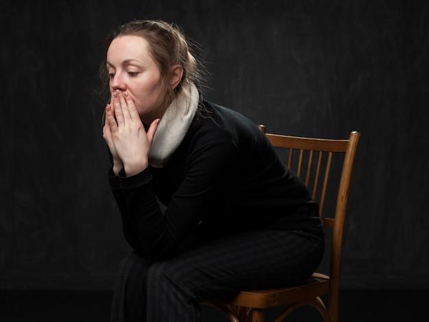 Jonge droevige gedesoriënteerde vrouwenzitting op de stoel
