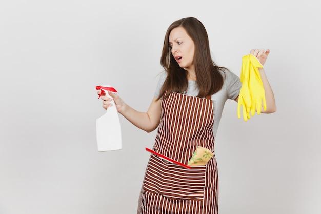 Jonge droevige overstuur vermoeide huisvrouw in gestreepte schort met poetslap in zak geïsoleerd op een witte achtergrond. vrouw houdt geur gele handschoenen spuitfles met schonere vloeistof. fles kopie ruimte.