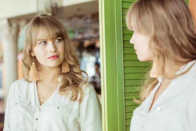 Jonge droevige vrouw die in de spiegel haar rimpels bekijkt