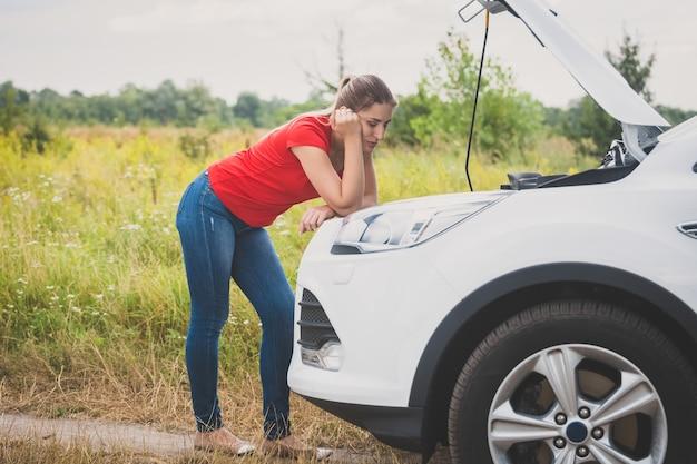 Jonge droevige vrouw die motor van gebroken auto bekijkt