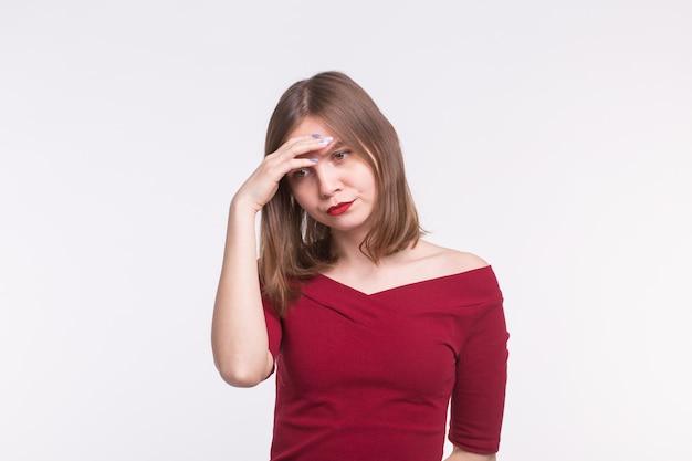 Jonge droevige vrouw met rode lippen die met hand op haar voorhoofd denken