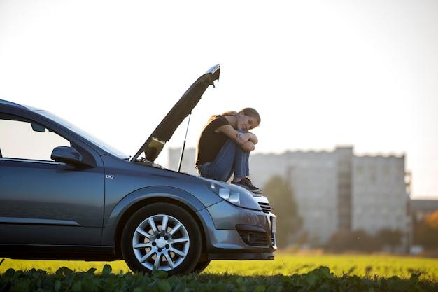 Jonge droevige vrouwenzitting op auto met geknalde kap in groene weide.
