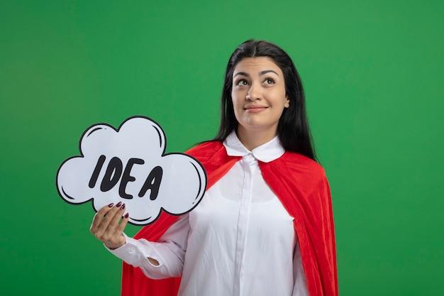 Jonge dromer kaukasische superheld meisje idee zeepbel houden en dromen opzoeken geïsoleerd op groene achtergrond met kopie ruimte