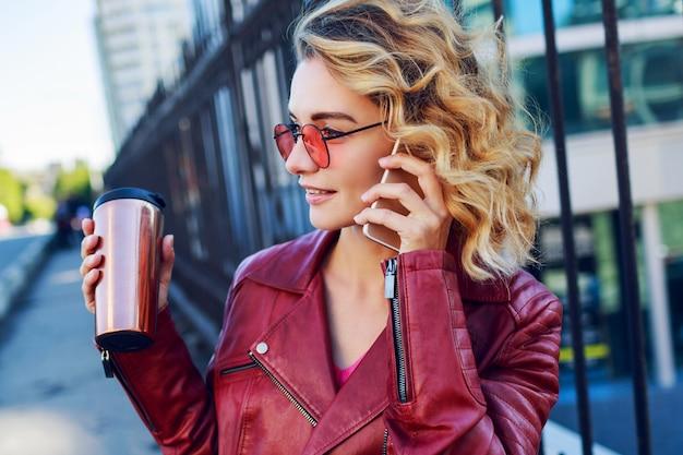 Jonge dromerige blonde vrouw die in de stad loopt en slimme telefoon met behulp van. sluit details. stijlvol modern meisje met koffie. winderige haren.