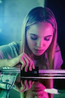 Jonge drugsverslaafde cocaïne lijn maken met zwarte creditcard op glazen oppervlak in het toilet van de nachtclub afterparty.