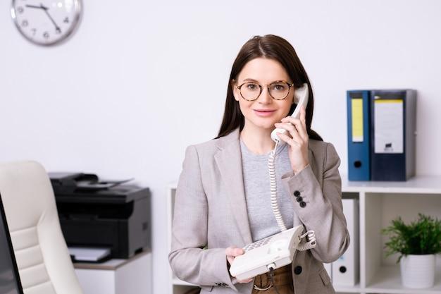 Jonge drukke brunette vrouwelijke officemanager in brillen en formalwear in gesprek met de klant aan de telefoon