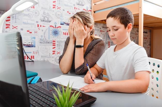 Jonge drukke moeder probeert thuis te werken met zijn kind. freelancer, thuiswerken, werken op afstand, freelancetaak.