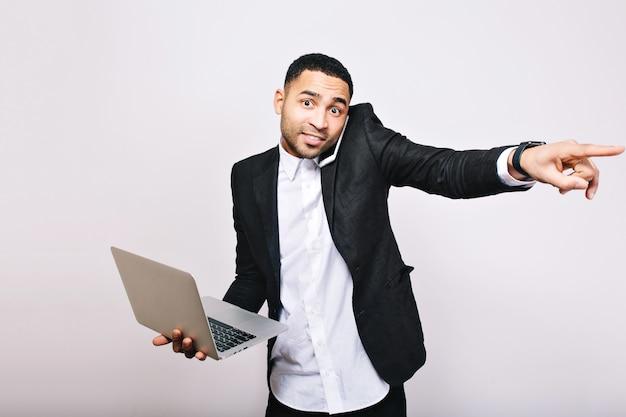 Jonge drukke vrolijke knappe kantoormedewerker in wit overhemd en zwarte jas met laptop, praten over de telefoon. zakenman, beroep, werkend, geweldige baas.