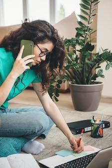 Jonge drukke vrouw heeft een telefoontje terwijl ze online videolessen op de vloer doet met behulp van een laptop