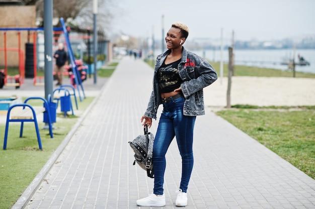 Jonge duizendjarige afro-amerikaanse meisje in de stad. gelukkig zwarte vrouw met draadloze koptelefoon. generatie z-concept.