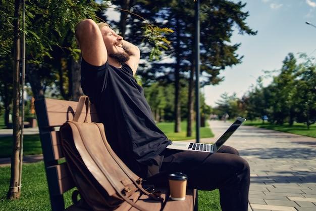 Jonge duizendjarige hipster man zit op de bank in het park met laptop en geniet van ontspannen vrije tijd