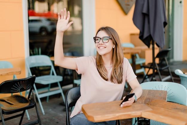 Jonge duizendjarige vrouw die telefoon in koffie met behulp van