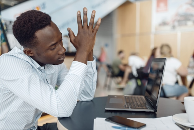 Jonge ebbenhout zakenman die aan laptop in bureaucafé werkt. succesvolle zakenman drinkt koffie in food-court, zwarte man in formele kleding