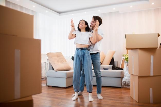 Jonge echtpaar in de woonkamer in het huis staan in de buurt van uitgepakte dozen. ze zijn blij met een nieuw huis. verhuizen, kopen van een huis, appartement concept.