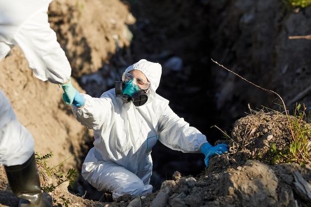 Jonge ecoloog in beschermend pak en masker werken in team in gevaarlijk gebied buitenshuis