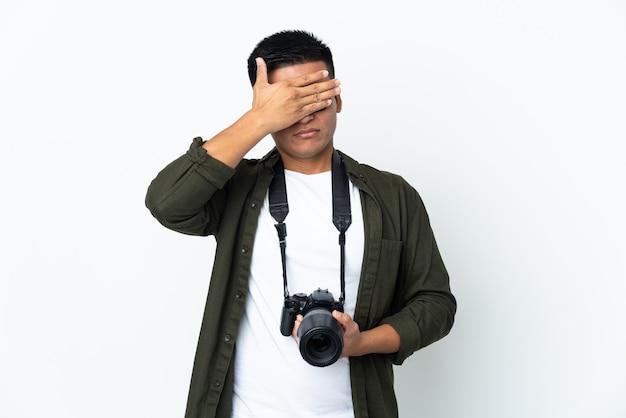 Jonge ecuadoraanse fotograaf die op witte achtergrond wordt geïsoleerd die ogen behandelt door handen. ik wil niets zien