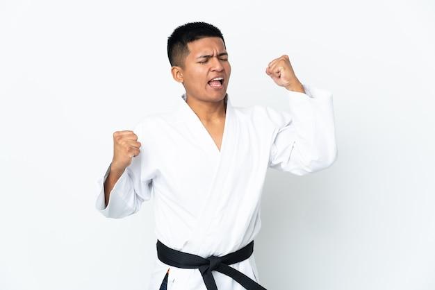 Jonge ecuadoraanse man doet karate geïsoleerd op een witte achtergrond die een overwinning viert
