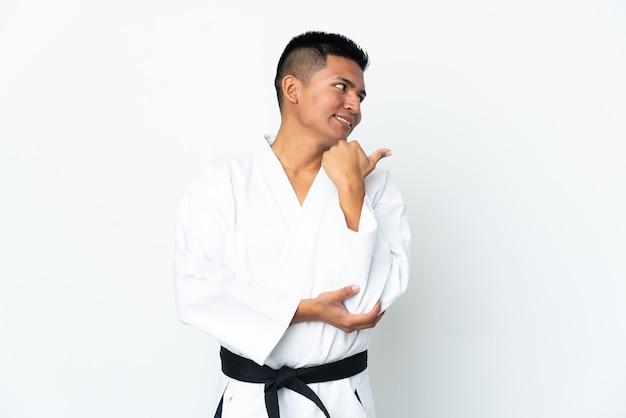 Jonge ecuadoraanse man doet karate geïsoleerd op een witte achtergrond die naar de zijkant wijst