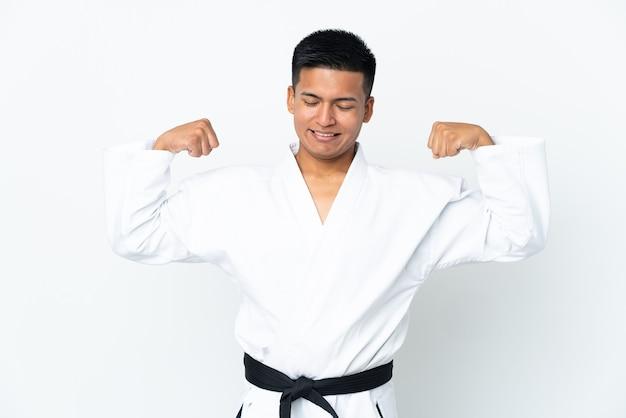 Jonge ecuadoraanse man doet karate geïsoleerd op een witte achtergrond die sterk gebaar doet