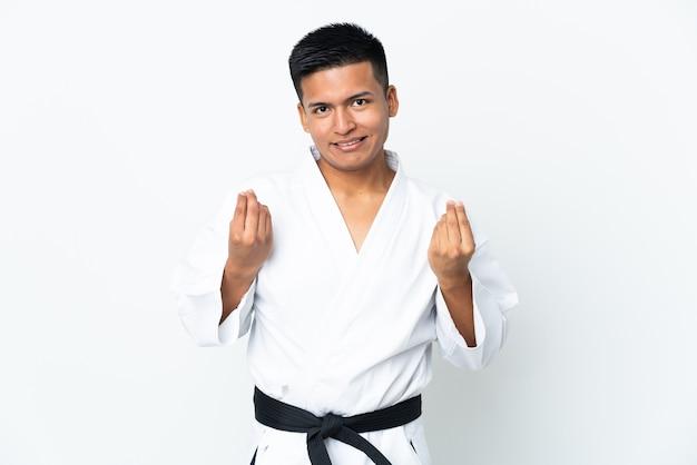 Jonge ecuadoraanse man doet karate geïsoleerd op een witte achtergrond geld gebaar maken