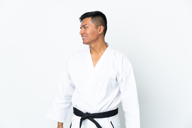 Jonge ecuadoraanse man doet karate geïsoleerd op een witte achtergrond, kijkend naar de zijkant en glimlachen