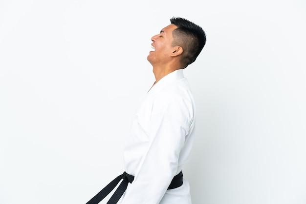 Jonge ecuadoraanse man doet karate geïsoleerd op een witte achtergrond lachend in zijpositie
