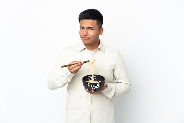 Jonge ecuadoraanse man geïsoleerd op een witte achtergrond met een kom noedels met stokjes